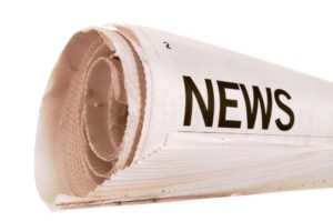 Rolled up newspaper with news headline set against a white background